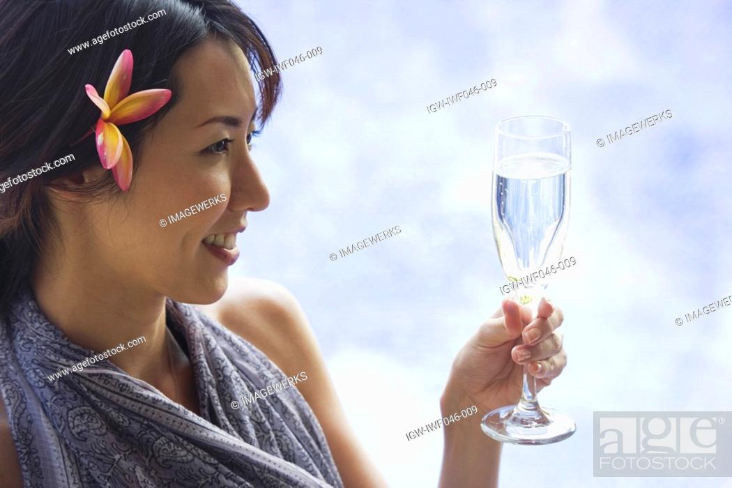 Stock Photo: View of a smiling young woman with drinks.