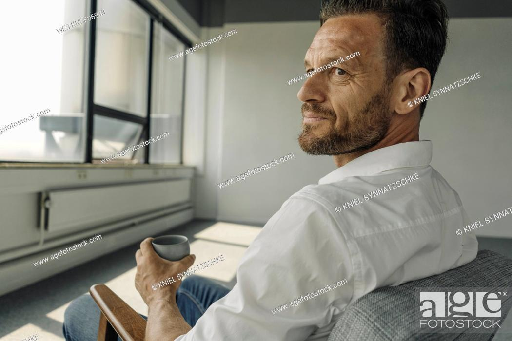 Stock Photo: Mature businessman with cup of coffee sitting in armchair in empty office.