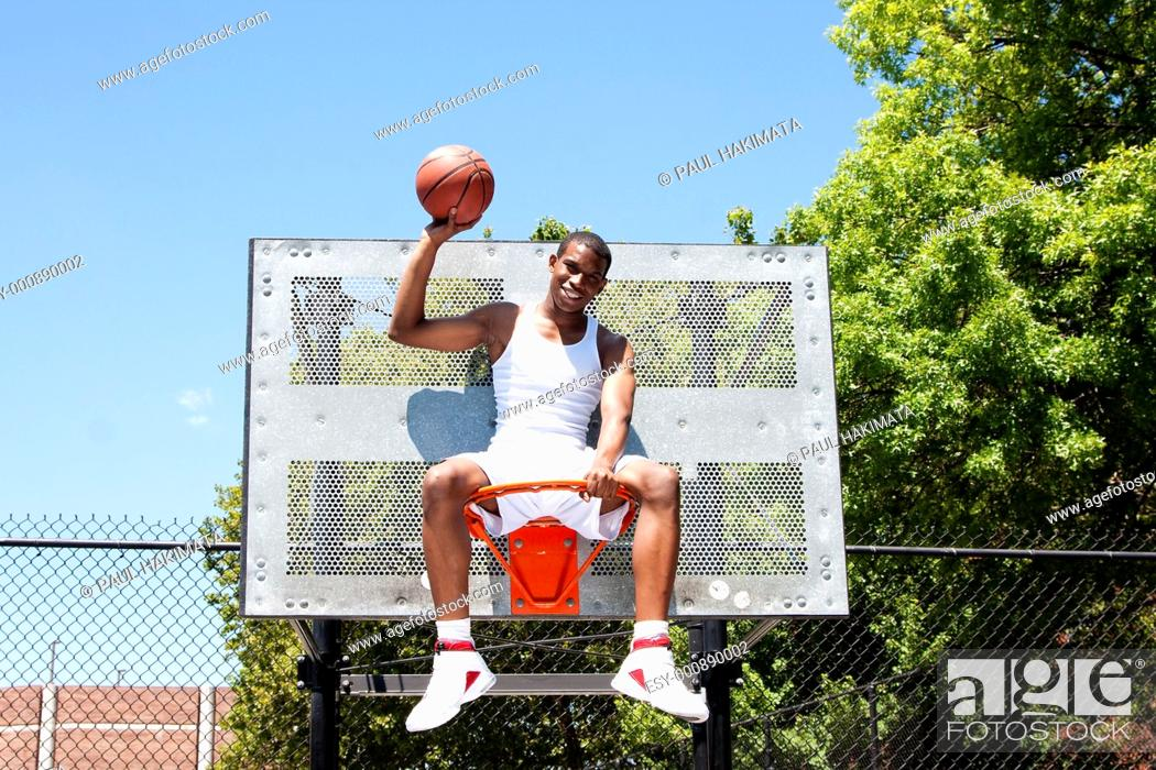 Stock Photo: Happy smiling handsome sporty African-American male basketball player dressed in white and holding his ball with one hand outdoor on a summer day in a.
