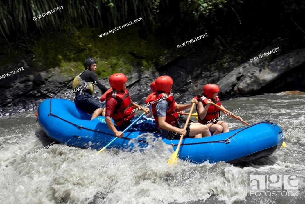 Stock Photo: Side profile of five people rafting in a river.