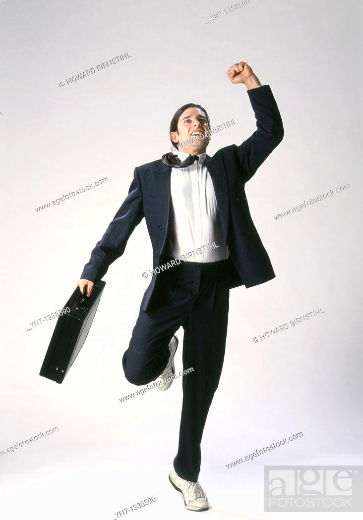 Stock Photo: Studio image of businessman in suit and runners triumphantly finishing his race.
