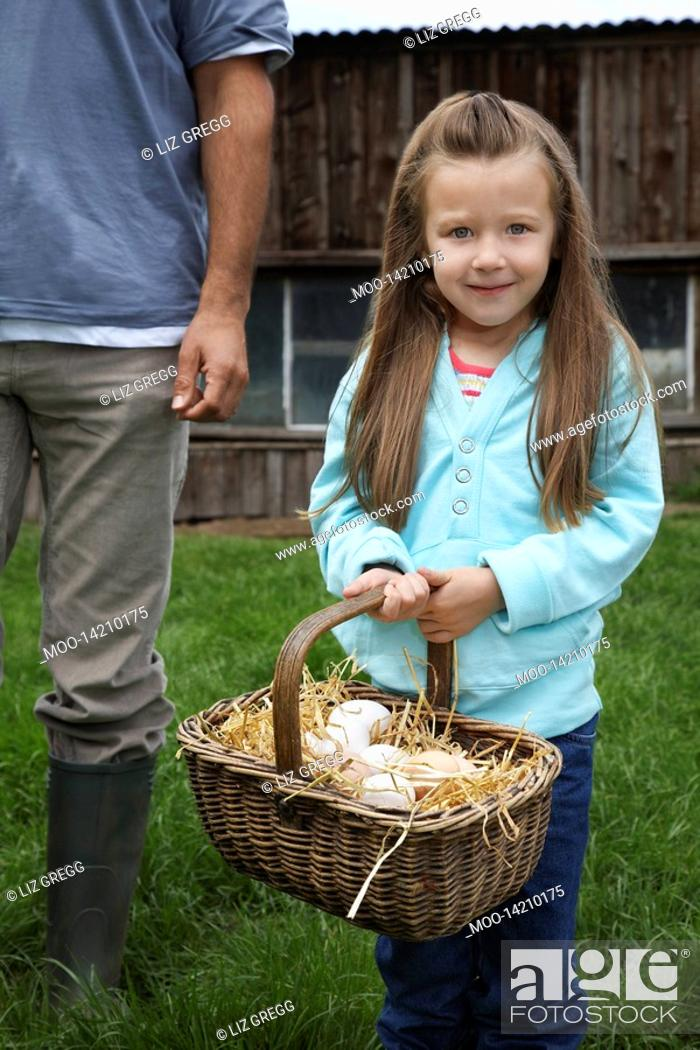 Stock Photo: Girl 5-6 holding egg basket father low section standing nearby outdoors portrait.