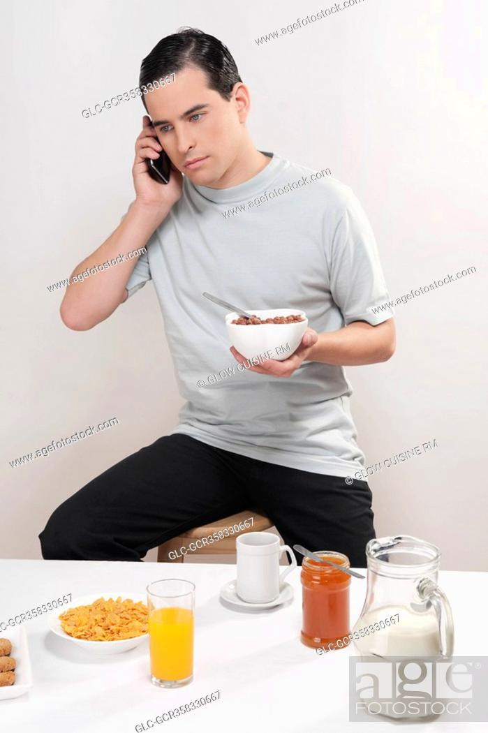 Stock Photo: Man talking on a mobile phone at breakfast.