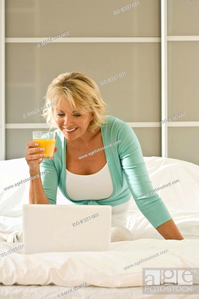 Stock Photo: Woman on bed with laptop.