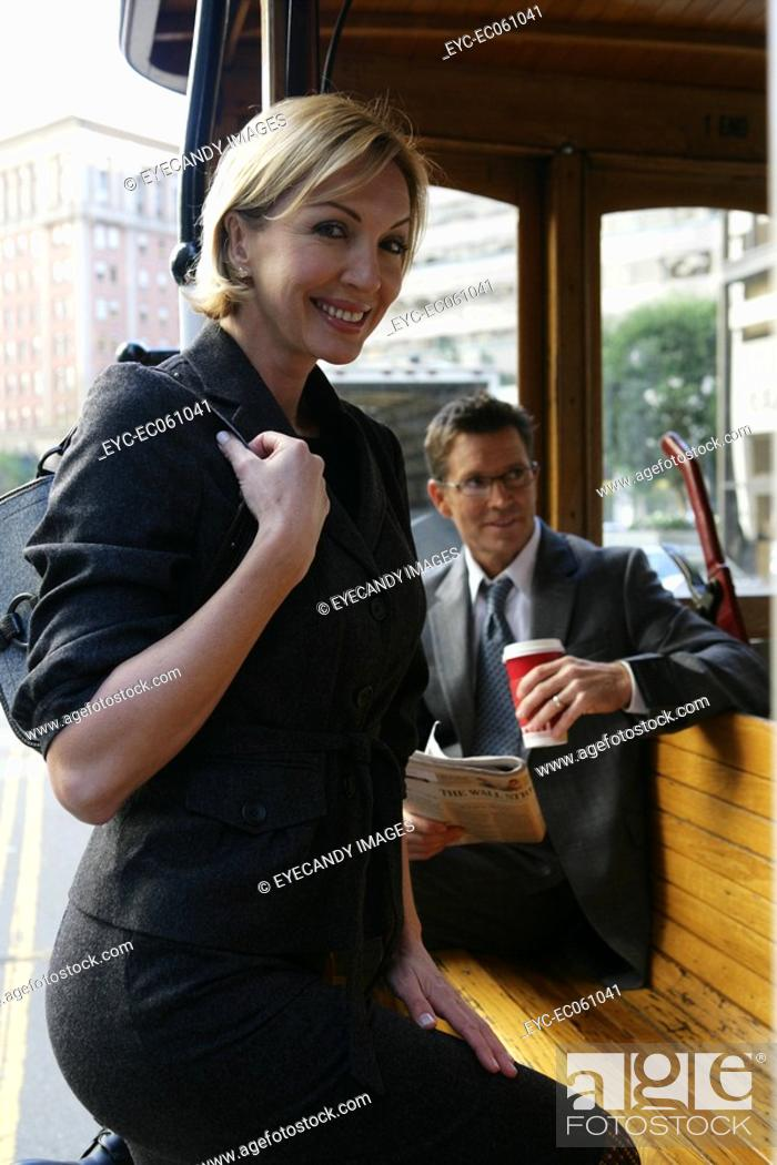 Stock Photo: Women stepping onto a trolley car, looking at camera.