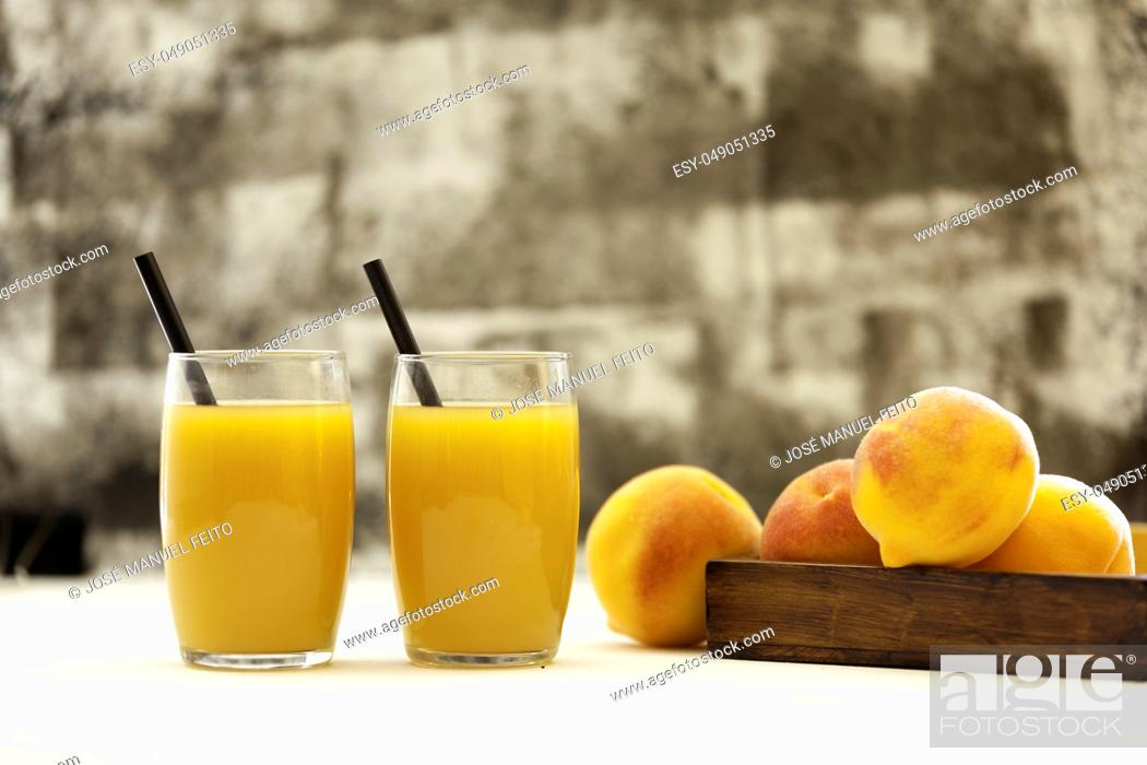 Stock Photo: two peach juice glasses with straws and peaches on wooden basket on white table and abstract backdrop.