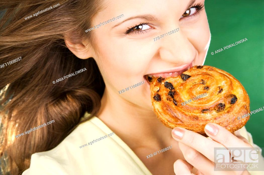 Stock Photo: Young woman eating yeast-cake.