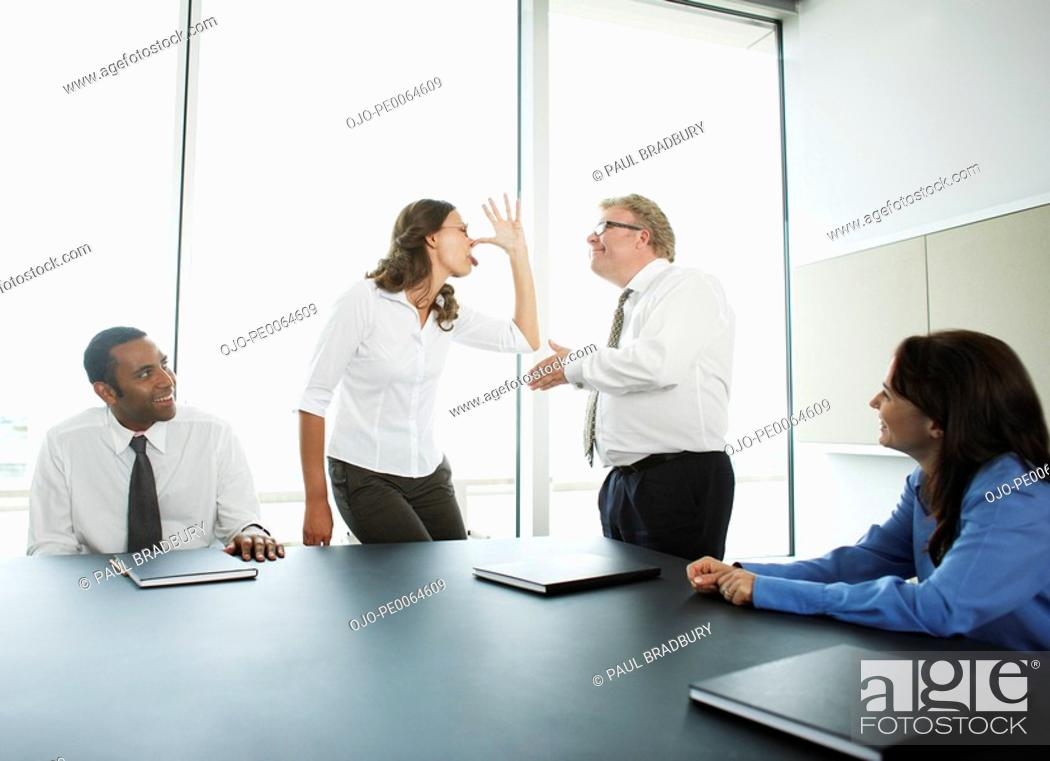 Stock Photo: Businesswoman making face at boss in conference room.