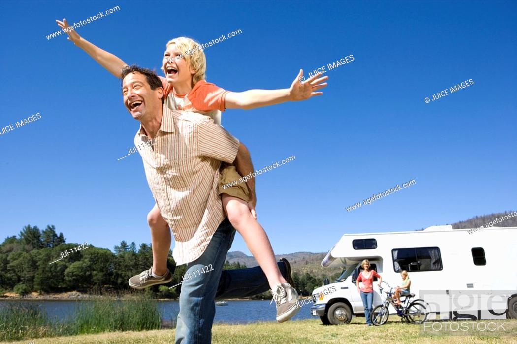 Stock Photo: Girl 9-11 on father's back, mother and brother 10-12 by motor home in background, low angle view.