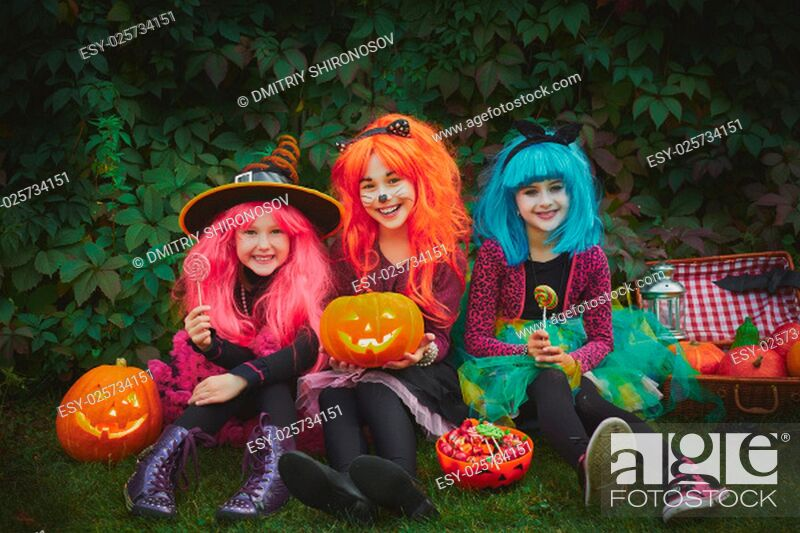Stock Photo: Happy girls with pumpkins and sweets celebrating Halloween outdoors.