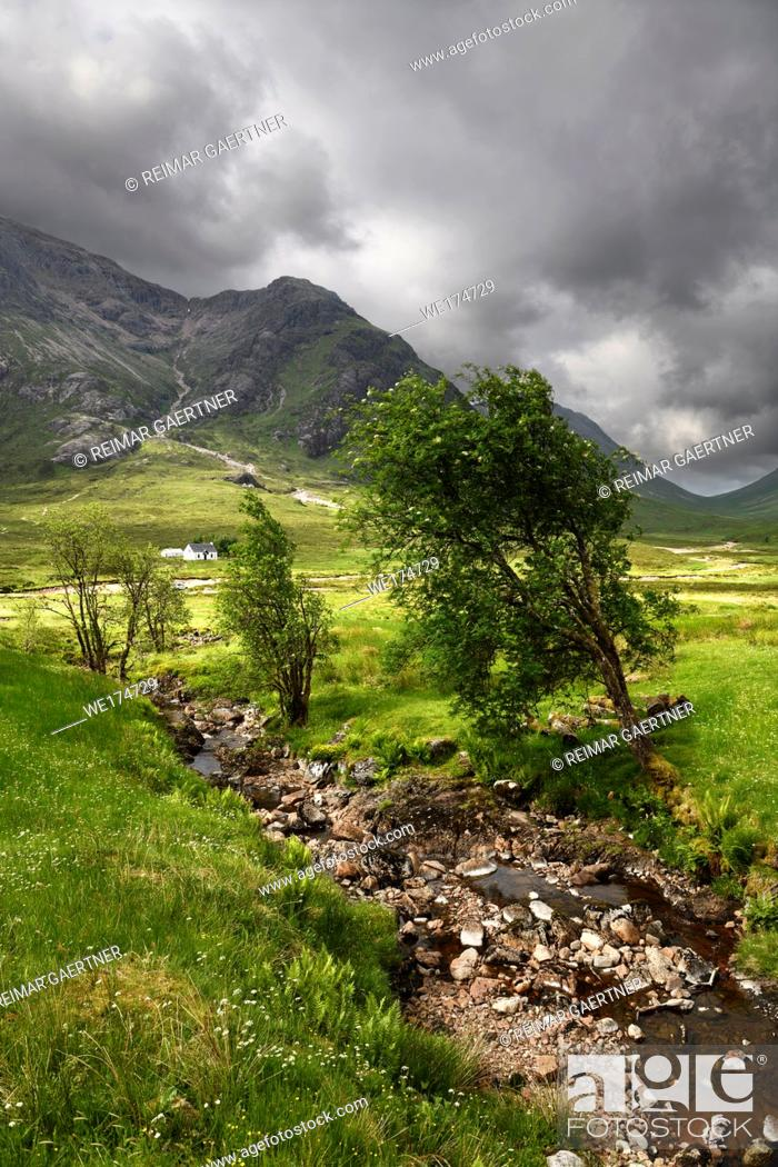 Stock Photo: Stream to River Coupall valley with white cottage at foot of Buachaille Etive Mor mountains Glen Coe under dark clouds Scotland UK.