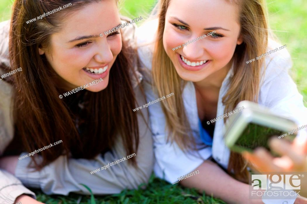 Stock Photo: Young friends laughing while photographing themselves.