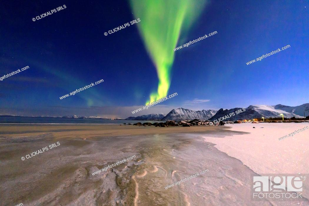 Stock Photo: The aurora borealis lights up the sky and the beach of the cold sea of Gymsøyand. Lofoten Islands Northern Norway Europe.