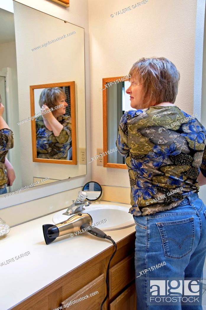 Stock Photo: This middle aged Caucasian woman is fixing her hair after blow drying it in the bathroom, looking in a mirror  An everday grooming moment lifestyle stock image.