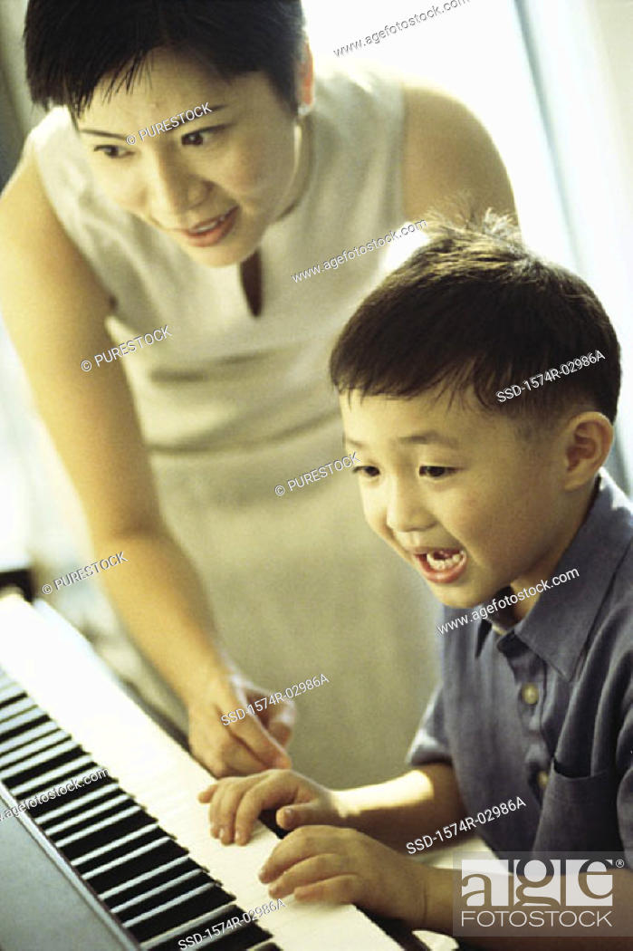 Stock Photo: Mother teaching her son the piano.