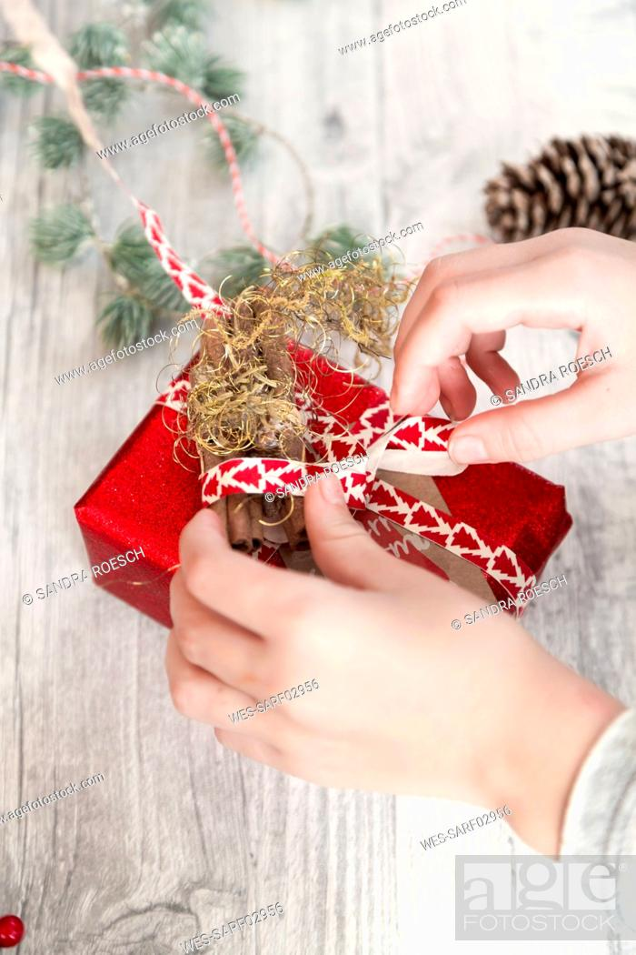 Stock Photo: Hands of girl wrapping Christmas present.