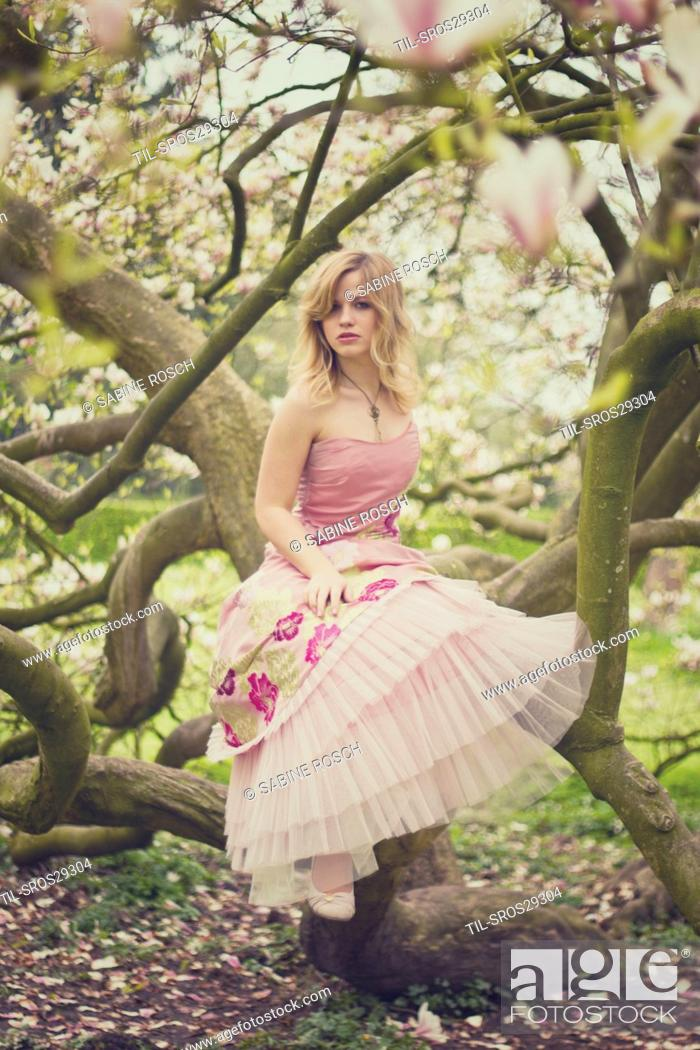 Imagen: A young blonde woman wearing a fancy pink dress in the sprintgime sitting at a magonlia tree.