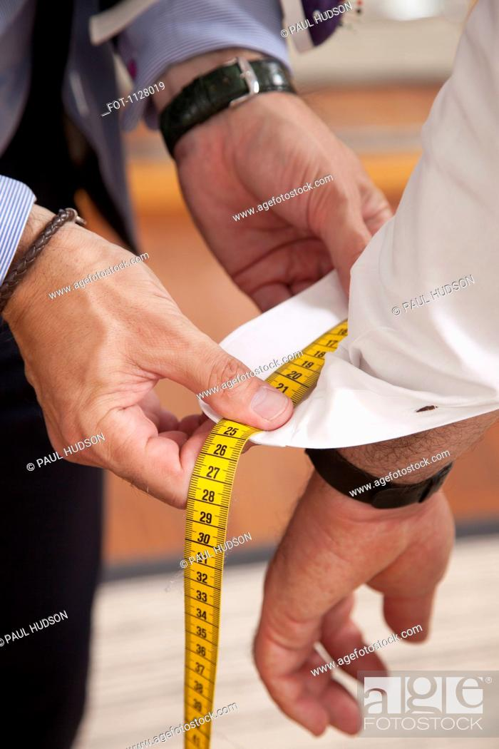 Stock Photo: Detail of a tailor measuring the shirt cuff of a man.