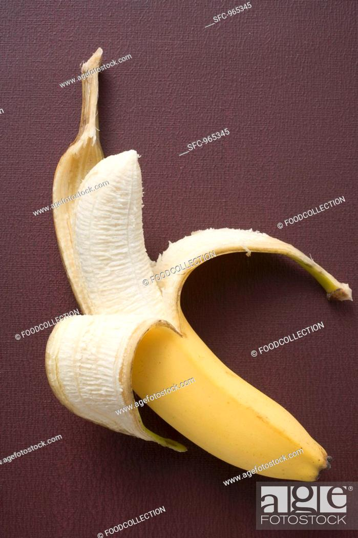 Stock Photo: Banana, half peeled, on brown background.