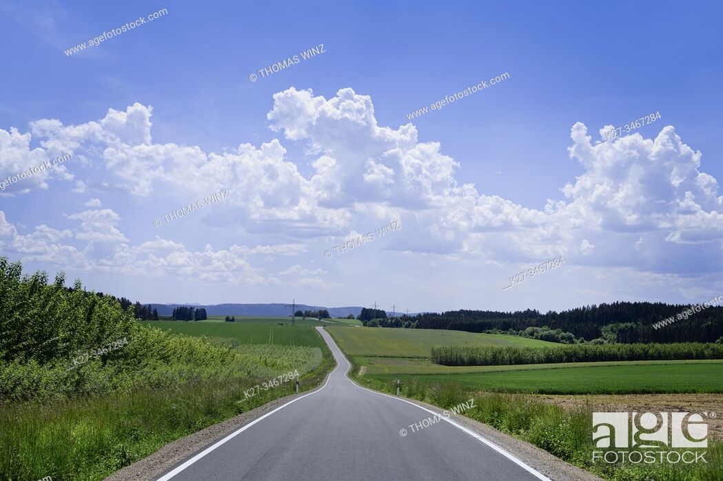 Stock Photo: Curving country road through agricultural fields and cloudscape, Baden Württemberg, Germany.