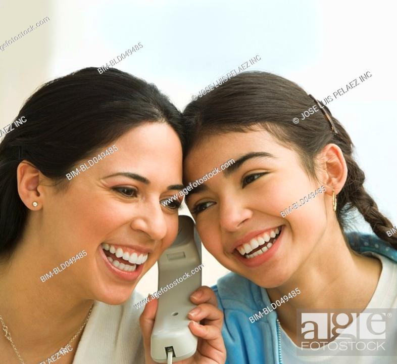 Stock Photo: Hispanic mother and daughter listening to telephone.