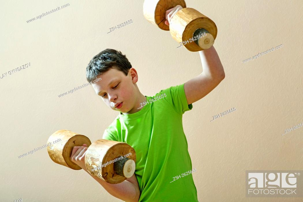 Stock Photo: Young athlete exercise with wooden dumbbells.