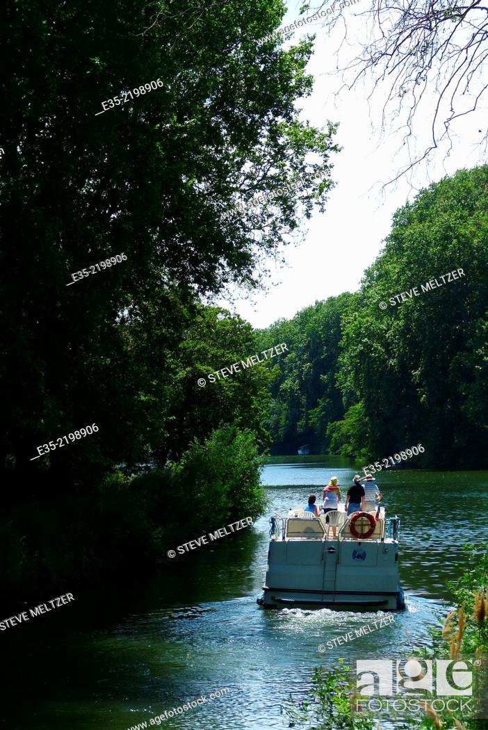Stock Photo: Piloting a rental boat down the Canal du Midi by Agde, France.