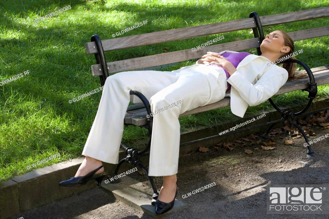 Stock Photo: Businesswoman sleeping on a bench in a park.