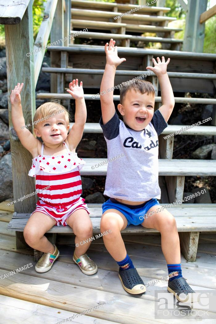 Stock Photo: Two happy kids raise their hands in celebration, sitting on stairs.