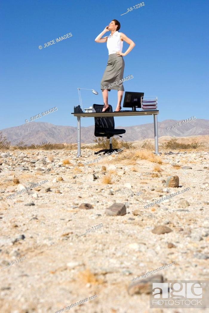 Stock Photo: Businesswoman standing on desk in desert, on telephone, low angle view.