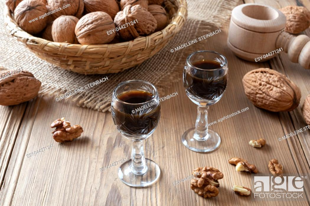 Stock Photo: Homemade nut liqueur with walnuts on a table.
