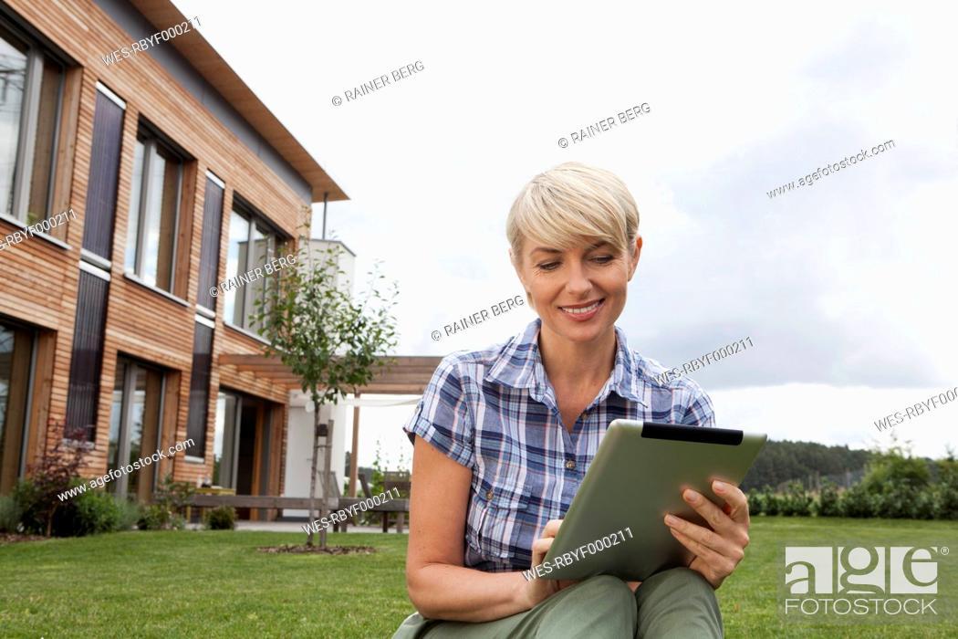 Stock Photo: Germany, Bavaria, Nuremberg, Mature woman using digital tablet in garden.