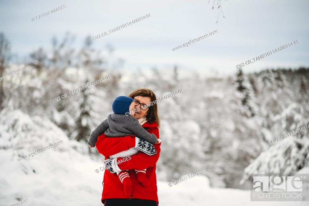 Stock Photo: Grandmother holding grandchild baby outside in snow in winter Norway.