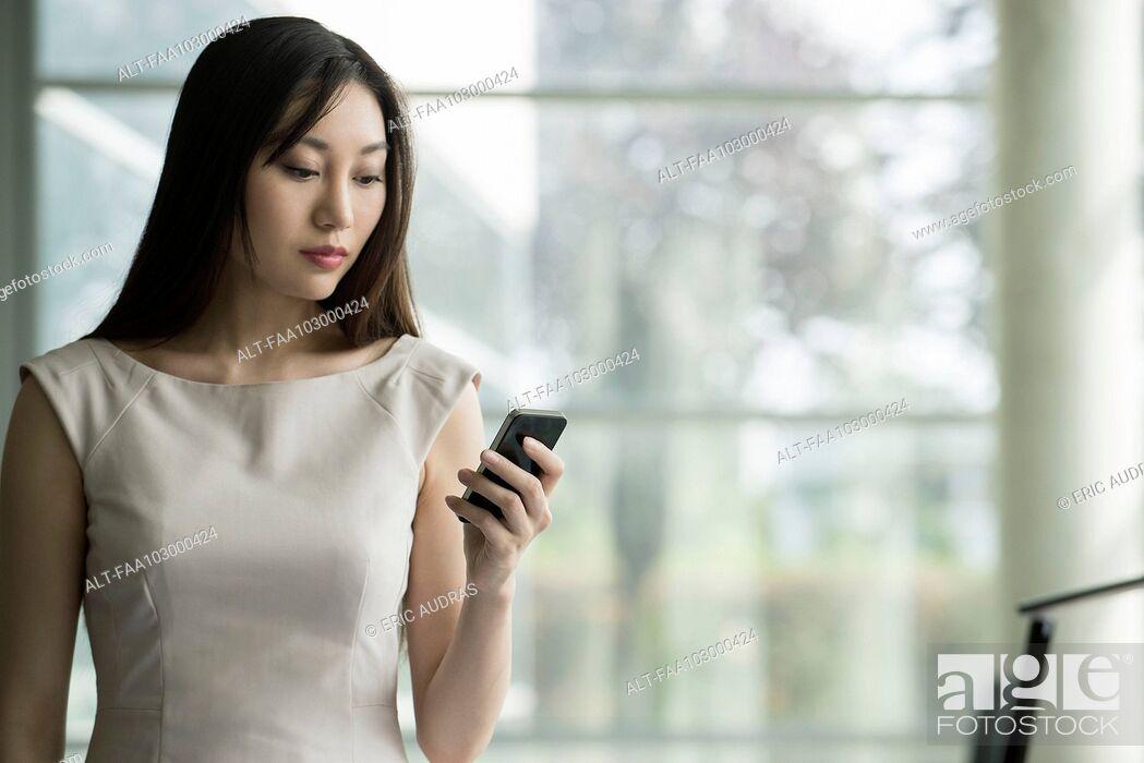 Stock Photo: Businesswoman using smartphone.