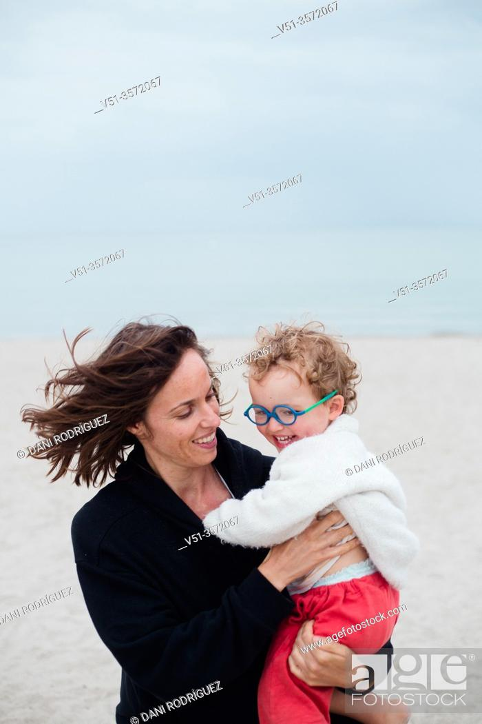 Stock Photo: 2 years old boy playing with his mother at the beach.