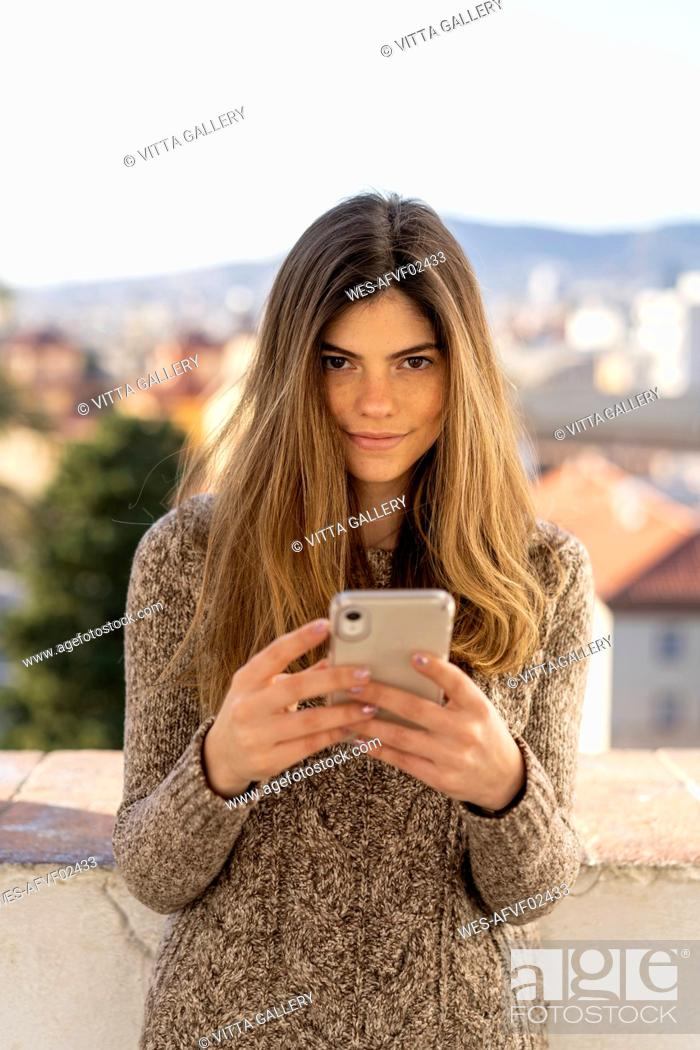 Stock Photo: Portrait of confident young woman holding cell phone.