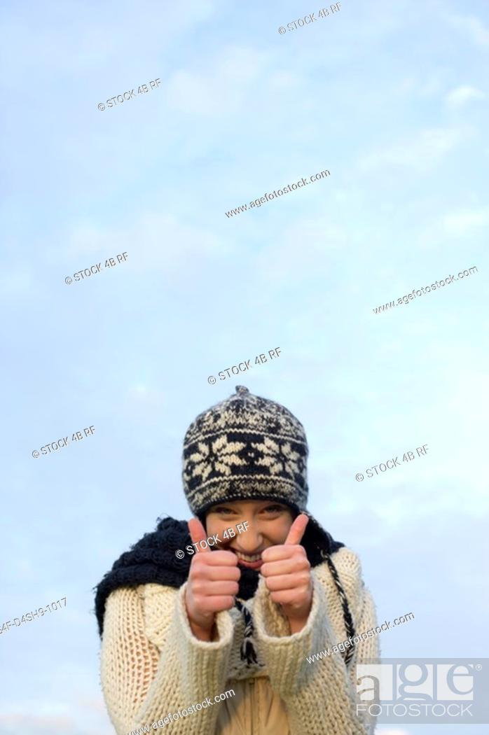 Stock Photo: Young woman with scarf and cardigan under the sky holding her thumbs up, close-up.