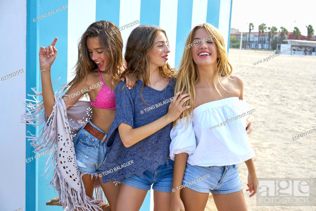 Stock Photo: Best friends teen girls group happy in a summer blue stripes background.