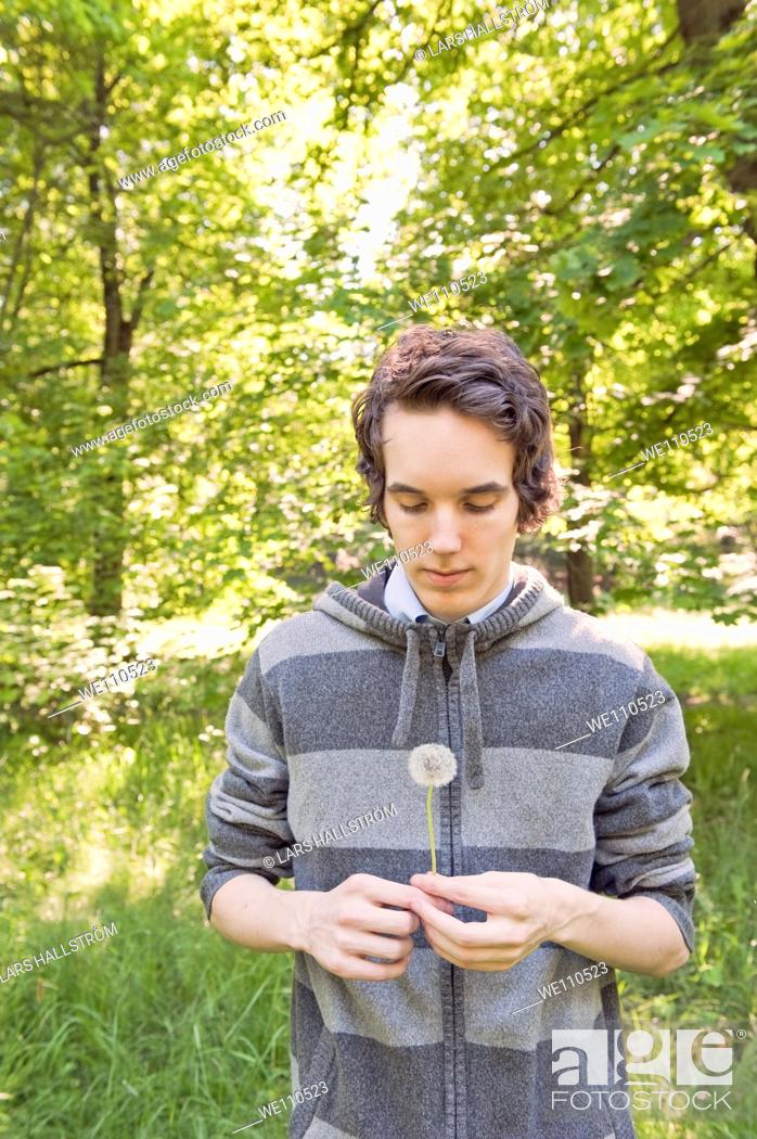 Stock Photo: Young man holding dandelion.