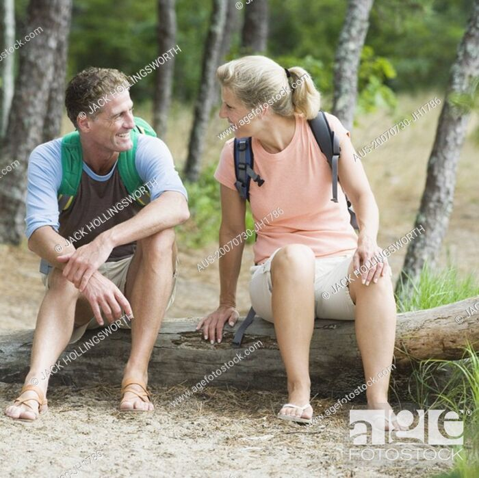 Stock Photo: Mature couple sitting on a tree trunk in a forest and looking at each other.