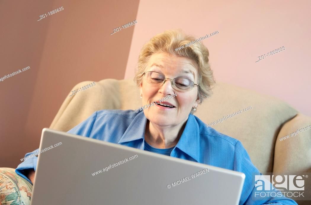 Stock Photo: Mature woman using laptop and smiling.
