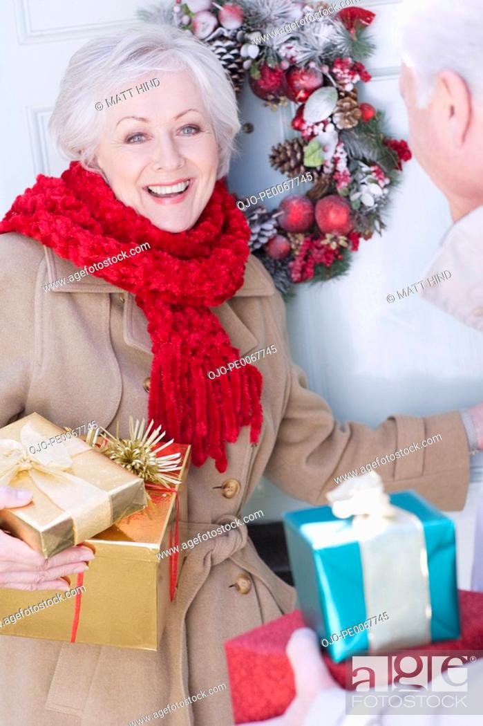 Stock Photo: Couple with Christmas gifts standing at door.