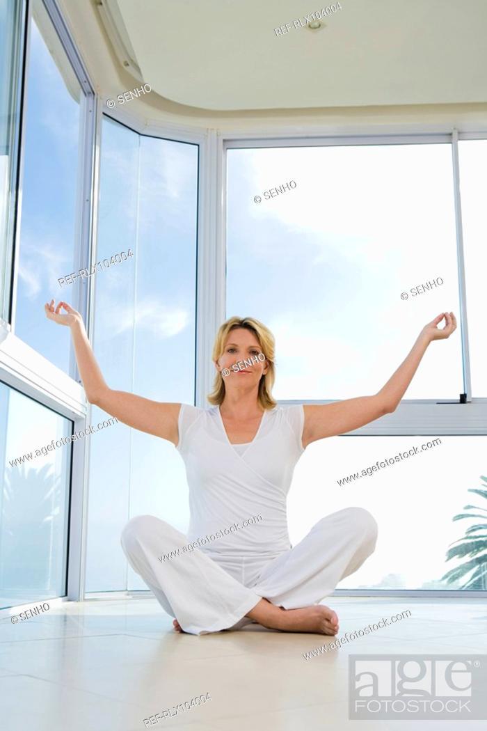 Stock Photo: Senior woman sitting, doing Yoga exercise, indoors.