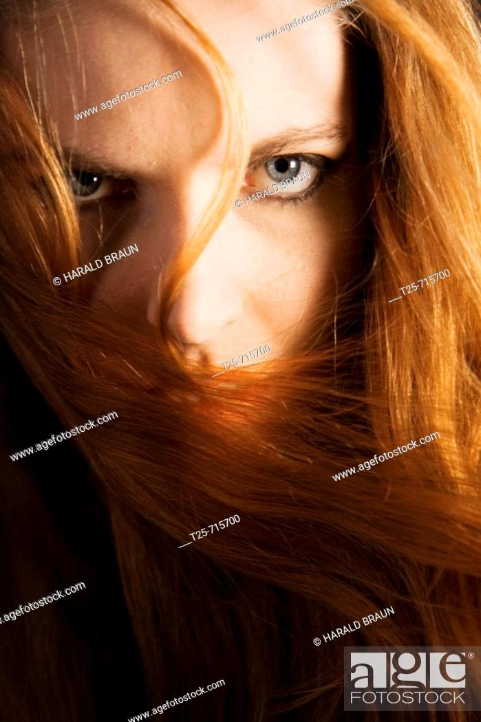 Stock Photo: Red haired woman gazing at camera.