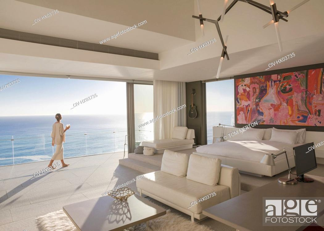 Stock Photo: Woman walking on sunny modern, luxury home showcase bedroom balcony with ocean view.