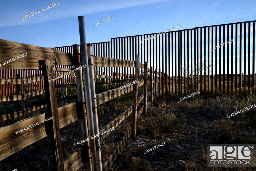 Stock Photo: A wall indicating the U. S. /Mexico border runs through the remains of corrals once used by ranchers from both sides of the border to house livestock while.
