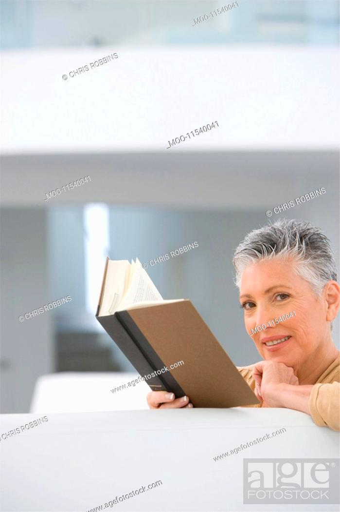 Stock Photo: Middle-aged woman reading book on sofa.