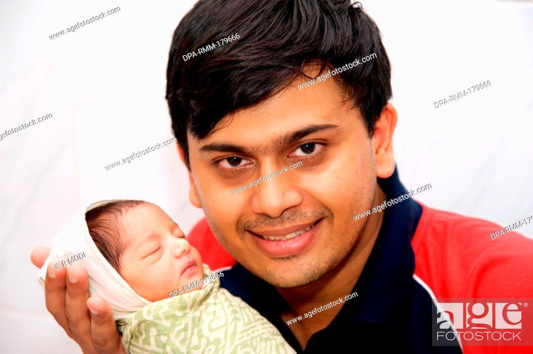 Indian man father holding newborn baby child white background, India