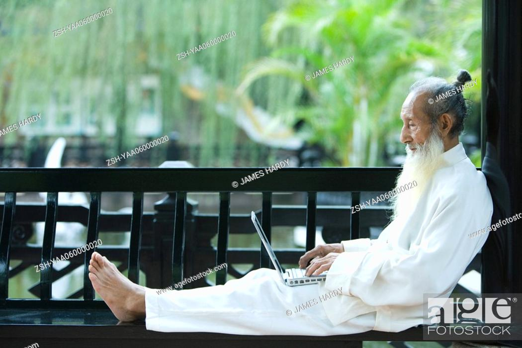 Stock Photo: Elderly man in traditional Chinese clothing, barefoot, using laptop.