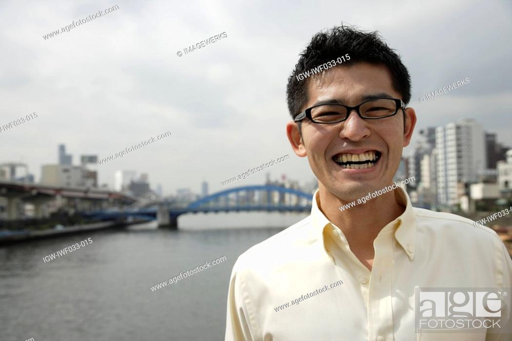Stock Photo: A smiling young man standing with river in background.